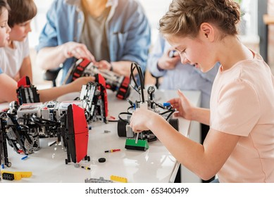 Concentrated smiling girl creating technical toy