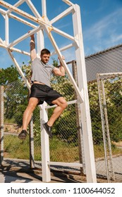 Concentrated sportsman doing pull ups on a basketball court outdoors