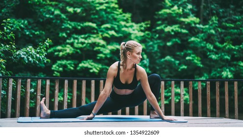 Concentrated sporty woman in stylish comfortable wear doing stretching exercises outdoors on green background during fitness training to better body shape, slimy girl in tracksuit losing cellulite
