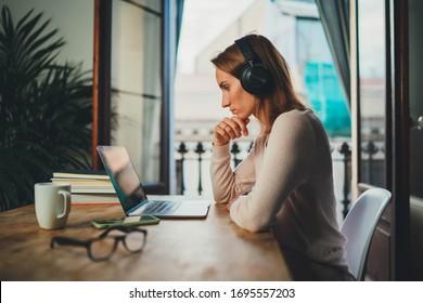 Estudiante concentrada aprendiendo en línea con videollamadas a través de una computadora portátil sentada en el interior cerca de un balcón abierto, empresaria que trabaja remotamente desde la oficina doméstica usando una computadora moderna