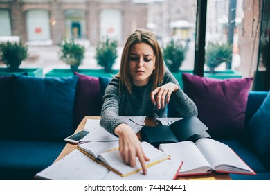 Concentrated student searching useful information for training project sitting in coffee shop interior at desktop with many papers and literature books.Pensive young woman preparing for upcoming exams