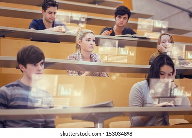 Concentrated students in lecture hall working on their futuristic tablet during lesson
