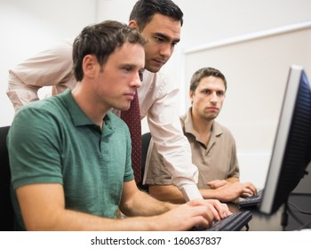 Concentrated teacher with mature students using computer in the computer room