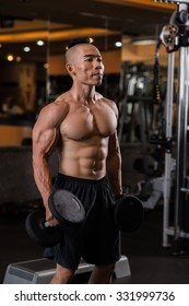Concentrated Vietnamese athlete working out with dumbbells