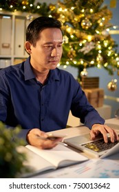 Concentrated Vietnamese businessman working on laptop in office decorated for Christmas