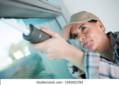 concentrated woman applying silicone to window