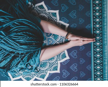 Concentrated woman with blue african braids praying with wooden rosary mala beads. Namaste. Close up hands on yoga mat with mandala. Top view.