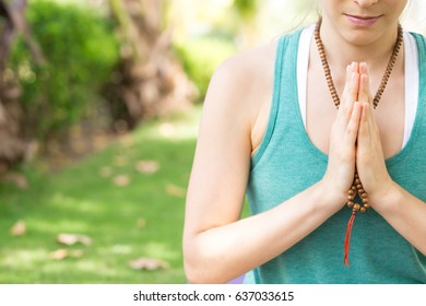 Concentrated woman praying wearing rosary beads
