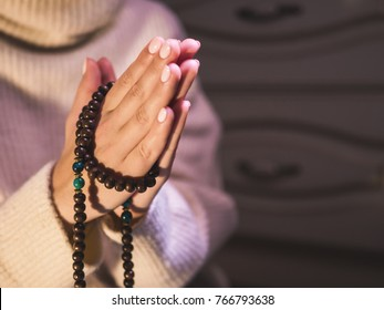 Concentrated woman praying wearing rosary beads. Namaste. Close up hands.