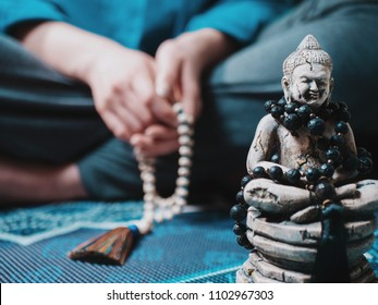Concentrated woman praying with wooden rosary mala beads. Namaste. Close up statue of Buddha.