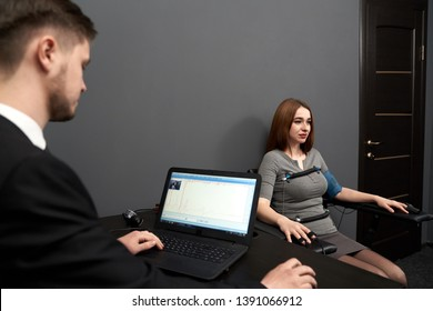 Concentrated woman sitting in grey room, testing at computer polygraph. Young man sitting at table and looking screen of polygraph and monitoring polygraph .