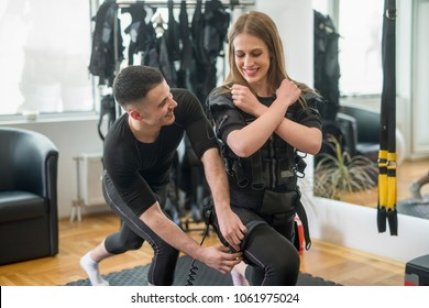 Concentrated woman working out ems training with his coach. Personal trainer helps the girl during the exercise