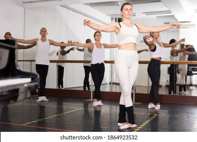 Concentrated women and men rehearsing ballet dance in studio.