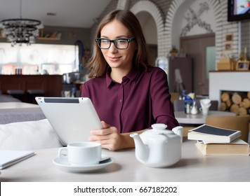 Concentrated at work. Confident young woman in smart casual wear working on laptop while sitting near window in creative office or cafe.
