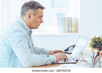 Concentrated at work. Side view of mature man working on laptop while sitting at his working place