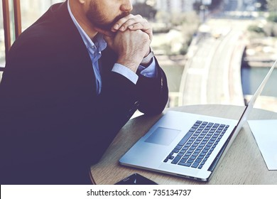 Concentrated and worried businessman sitting front open net-book in his office, male entrepreneur reading the financial breakdown of his budget while using laptop computer during work day in company