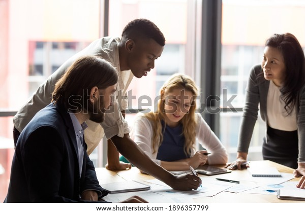 Concentrated young african american employee analyzing marketing research results or sales statistics data at briefing meeting with motivated older korean and young caucasian colleagues in office.