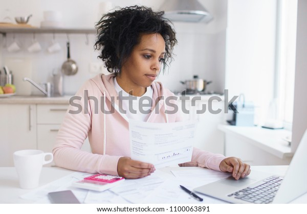 Concentrated young african american female student using online banking application with hand on touchpad, looking at screen of his laptop, trying to make payment for university education