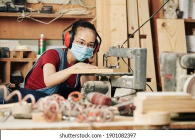 Konzentrierter junger asiatischer Tischler in Ohrmuffen und medizinische Maske Schneiden von Holzschnitzeln für Möbelartikel arbeitet sie an