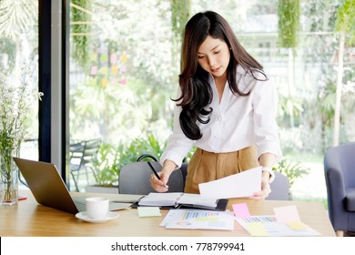 Concentrated young Asian women working on laptop while standing at working place.