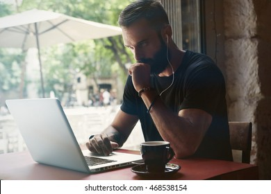 Concentrated Young Bearded Businessman Wearing Black Tshirt Working Laptop Urban Cafe.Man Sitting Wood Table Cup Coffee Looking Through Window.Coworking Process Business Startup.Blurred Background.