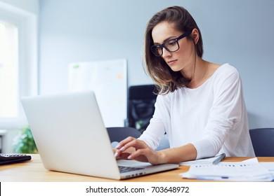 Konzentrierte junge schöne Geschäftsfrau, die auf Laptop in einem hellen, modernen Büro arbeitet