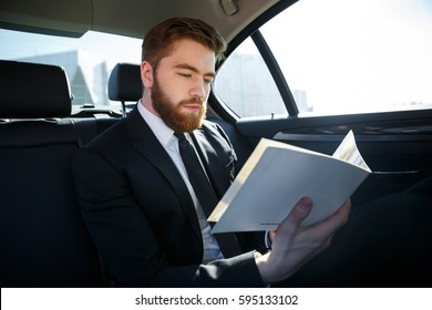 Concentrated young businessman analyzing documents while traveling in a back seat of a car