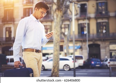 Concentrated young businessman with briefcase reading financial news walking in architecture town using 4G internet connection on cellphone. Copy space area for your advertising text message