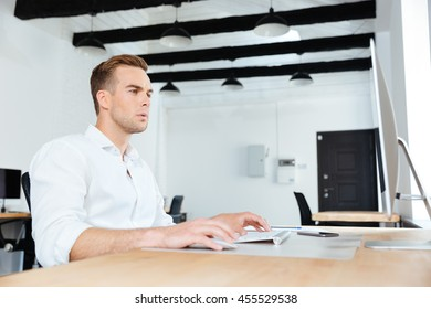 Concentrated young businessman sitting and working with computer at workplace