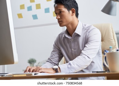 Concentrated young businessman working on computer in office