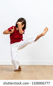 concentrated young child showing grace and positive energy with fighting legs and arms for kid's martial art and positive energy over wooden floor, white background