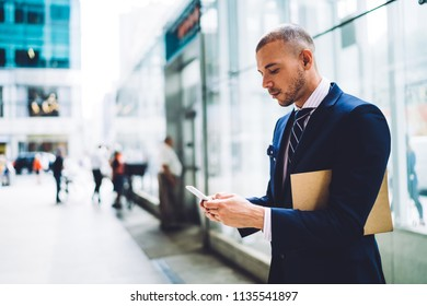 Concentrated young entrepreneur dressed in formal wear typing text notification in online chat on smartphone using 4G internet connection.Pensive proud ceo with folder searching information on website