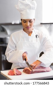 Concentrated young female chef cutting meat in the kitchen