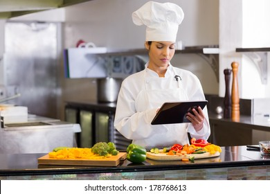 Concentrated young female chef using digital tablet while cutting vegetables in the kitchen