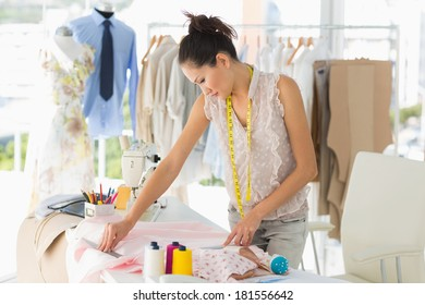 Concentrated young female fashion designer working on fabrics in the studio