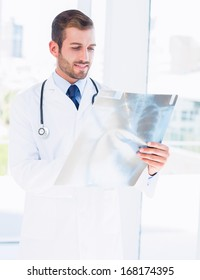 Concentrated young male doctor examining x-ray in the medical office