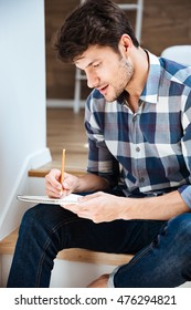 Concentrated young man in checkered shirt sitting and writing in notepad at home