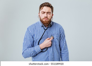 Concentrated young man with closed eyes using stethoscope and feeling heartbeat