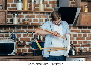 concentrated young man in eyeglasses repairing stool in kitchen