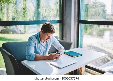 Concentrated young man installing application on mobile making settings while resting in cafe interior, pensive hipster guy making money transaction online browsing website of bank on smartphone