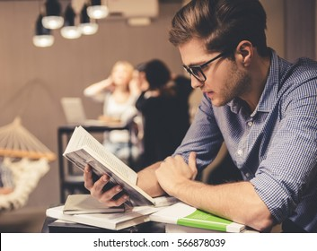 Concentrated young man is reading a book while working hard in the modern library