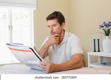 Concentrated young man reading newspaper at home