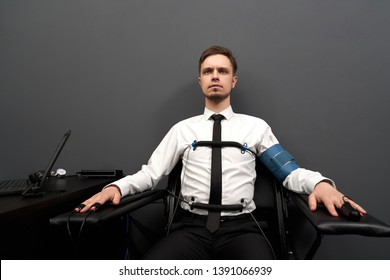 Concentrated young man sitting in black chair with attaching sensors on fingers and  body. Handsome man passing check with lie detector in grey room, looking at camera.