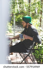 concentrated young man sitting with laptop and cup of coffee on terrace with a lot of green plants around