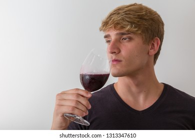 Concentrated young man sommelier with red wine in glass over white background