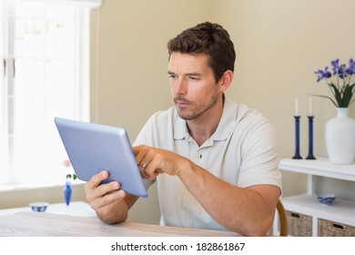 Concentrated young man using digital tablet on table at home