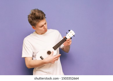 Concentrated young man in a white T-shirt stands on a blue background with a ukulele in hands and looks at the strings carefully.Serious guy with ukulele isolated.Portrait of a musician with ukulele