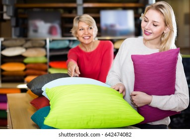concentrated young and senior female customers looking through pillows in home textile shop