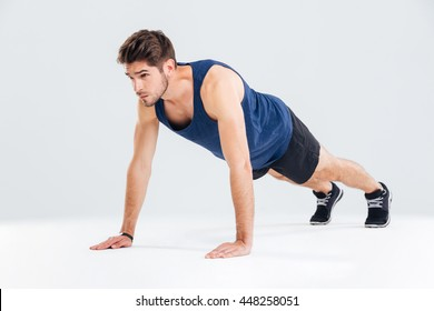 Concentrated young sportsman exercising and doing push ups over white background