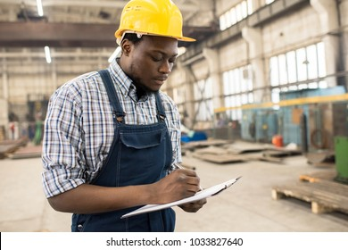 Concentrated young technician wearing overall and protective helmet standing at spacious production department of modern plant and taking notes while taking inventory